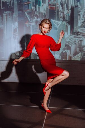 attractive and stylish woman in red dress on city background