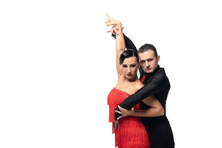 passionate couple of dancers looking at camera while performing tango isolated on white