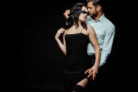 passionate bearded man touching dress of blindfolded girlfriend isolated on black
