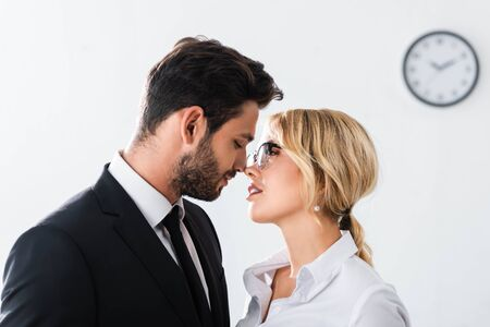 Side view of business couple looking at each other while flirting in office