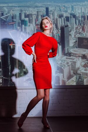 attractive and stylish woman in red dress with hands on hips on city background