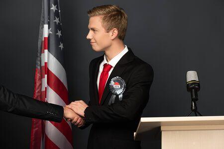 KYIV, UKRAINE - OCTOBER 18, 2019: smiling man shaking hand while imitating Donald Trump on tribune with american flag on black background Фото со стока
