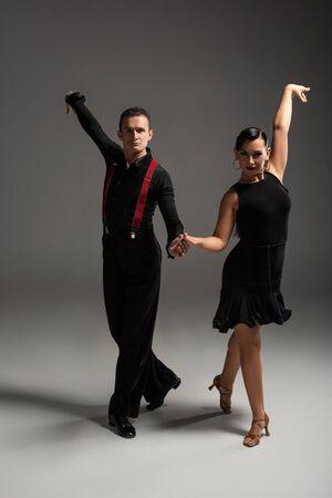 elegantes bailarines en ropa negra mirando a la cámara mientras bailan tango sobre fondo gris