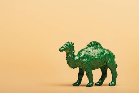 Green toy camel on yellow background, animal welfare concept