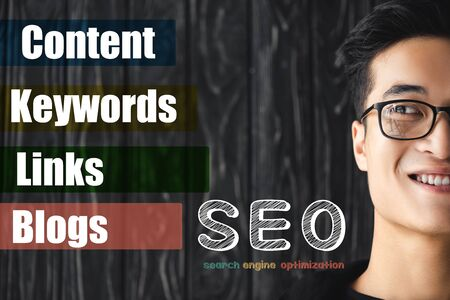 cropped view of smiling asian seo manager looking at illustration with concept words of seo