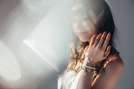 happy boho girl with braids in hairstyle posing on grey with lens flares Stock fotó