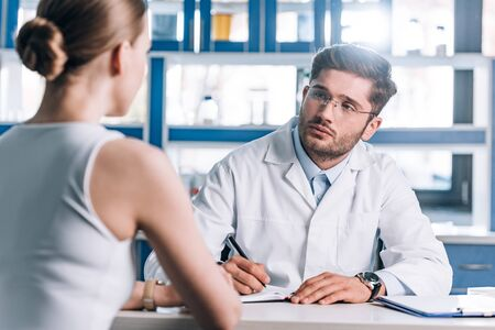 selective focus of handsome doctor holding pen and looking at patient Imagens