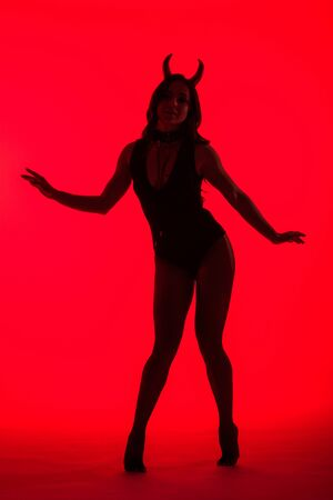 silhouette of attractive woman in Devil costume, isolated on red