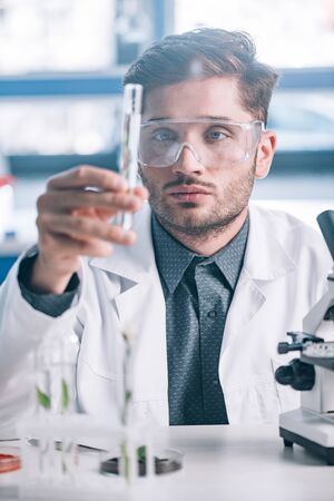 selective focus of handsome biochemist in goggles holding glass test tube