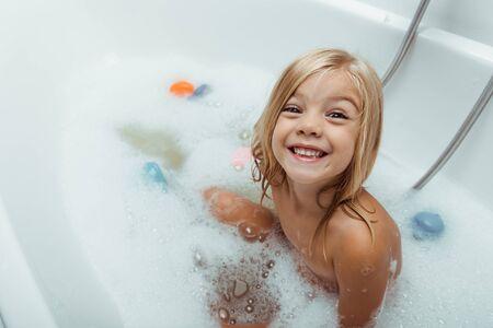happy child taking bath with bath foam at home