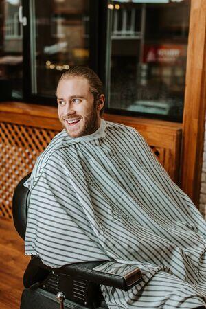 happy bearded man in stripped barbers cape sitting in barbershop