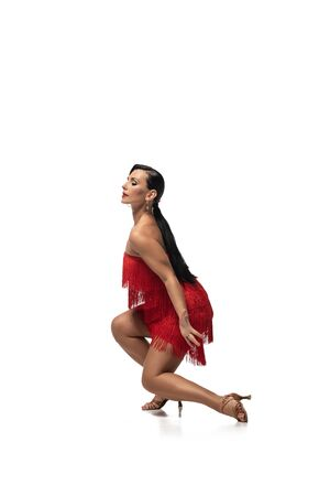 elegant dancer squatting with closed eyes while performing tango on white background Foto de archivo
