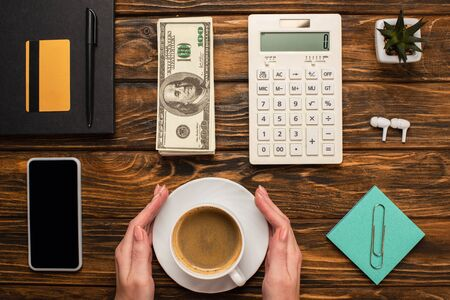 cropped view of businesswoman holding coffee cup near smartphone, dollar banknotes,  calculator, wireless earphones and stationery on wooden desk
