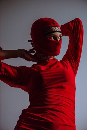 stylish woman in red dress and balaclava isolated on grey Reklamní fotografie