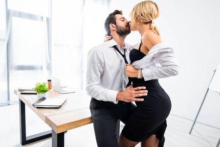 Secretaria sexy tentador empresario en la mesa de oficina