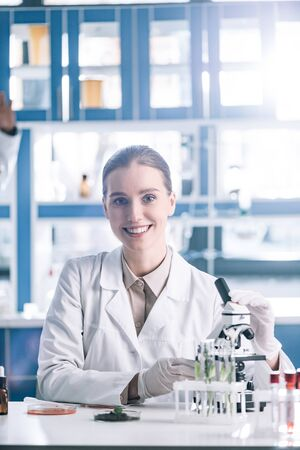 selective focus of happy scientist in white coat near microscope Stock Photo