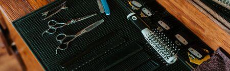 panoramic shot of sharp scissors near hair brush in barbershop Stock fotó