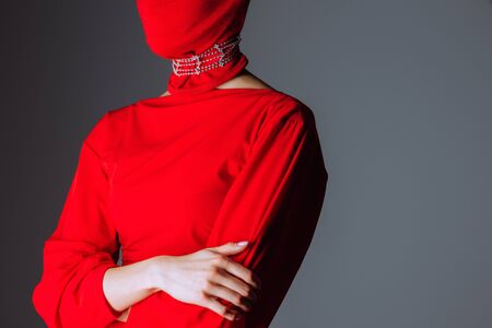 cropped view of woman in red dress and balaclava isolated on grey Zdjęcie Seryjne