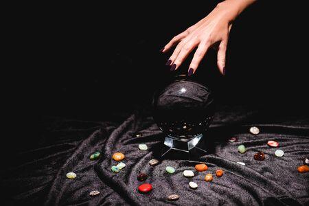vue recadrée de la main de diseur de bonne aventure au-dessus de la boule de cristal avec des pierres de divination sur un tissu de velours noir isolé sur noir
