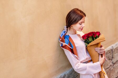 pensive girl holding bouquet of red roses while standing near wall