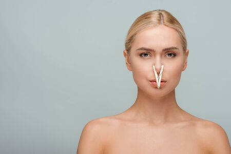 beautiful and naked young woman with wooden pin on nose isolated on grey Imagens