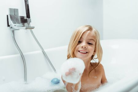 happy naked kid looking at bath foam on hand while taking bath