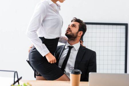 Ausgeschnittene Ansicht einer Geschäftsfrau, die einen Geschäftsmann am Arbeitsplatz berührt Standard-Bild