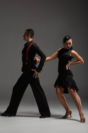 stylish couple of dancers in black clothing performing tango on grey background