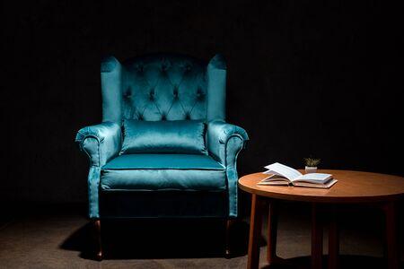 Eleganter blauer Sessel aus Velours in der Nähe eines Holztischs mit Buch isoliert auf Schwarz