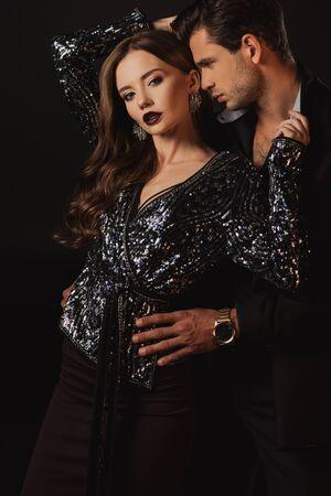 bell'uomo in tuta che abbraccia una donna attraente isolata sul nero