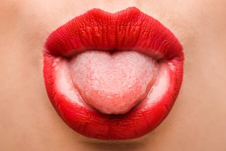 cropped view of girl with red lipstick sticking out tongue isolated on white