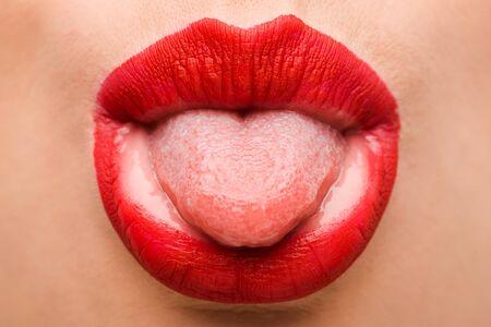 Vista recortada de niña con lápiz labial rojo lengua fuera aislado en blanco