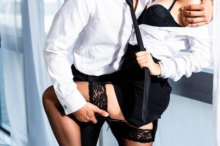 Ausgeschnittene Ansicht einer Sekretärin in Strümpfen, die die Krawatte des Geschäftsmannes zieht Standard-Bild