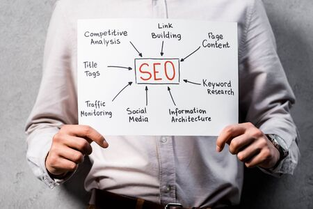 cropped view of seo manager holding paper with concept words of seo Stock Photo