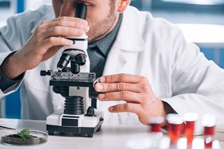 cropped view of bearded biochemist looking through microscope in laboratory  Stock Photo
