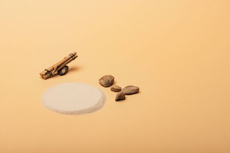 Sand with stones and wooden sticks on yellow background, animal habitat concept