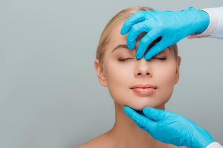 cropped view of beautician in latex gloves touching nose of woman isolated on grey