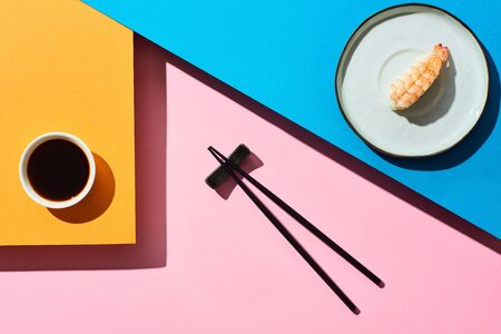 top view of fresh nigiri with shrimp near soy sauce and chopsticks on blue, pink, orange background Фото со стока