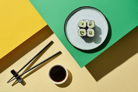 top view of fresh nigiri with cucumber near soy sauce and chopsticks on green and yellow surface