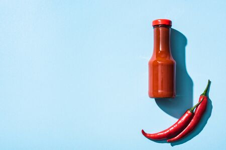 Top view of chili sauce and raw chili peppers on blue background