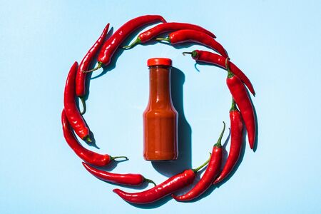 Top view of round frame of chili peppers around bottle with tasty chili sauce on blue background Standard-Bild