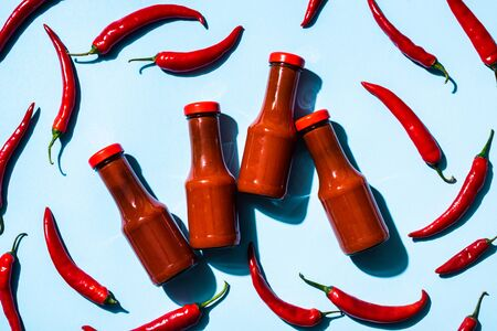 Top view of bottles with homemade chili sauce and chili peppers on blue background