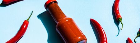 Chili sauce with chili peppers on blue background, panoramic shot Standard-Bild