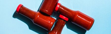 Top view of bottles with tasty tomato sauce on blue surface, panoramic shot Standard-Bild