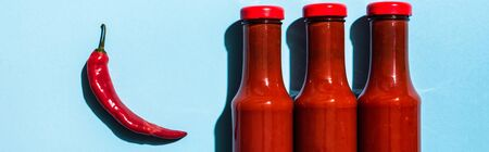 Top view of ripe chili pepper beside chili sauce in bottles on blue background, panoramic shot