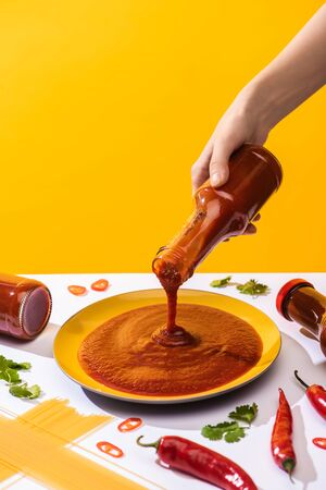 Cropped view of woman holding ketchup beside spaghetti and chili peppers on white surface isolated on yellow Standard-Bild