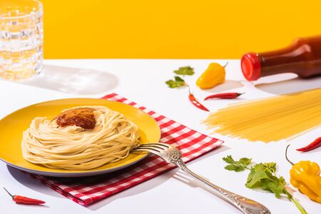 Tasty spaghetti with ketchup beside peppers and glass of water on white surface on yellow background Standard-Bild