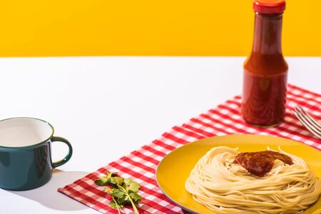 Prepared spaghetti with tomato sauce beside cup on white surface on yellow background Standard-Bild