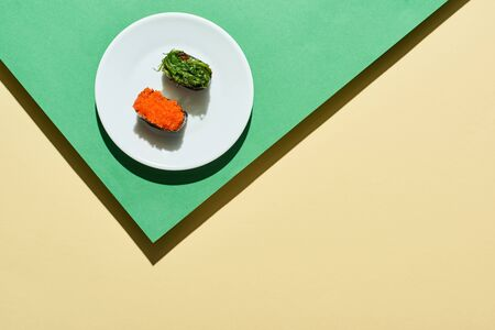 top view of fresh nigiri with red caviar and seaweed on green and yellow surface