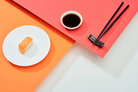 fresh nigiri with salmon near soy sauce and chopsticks on red, orange, white surface